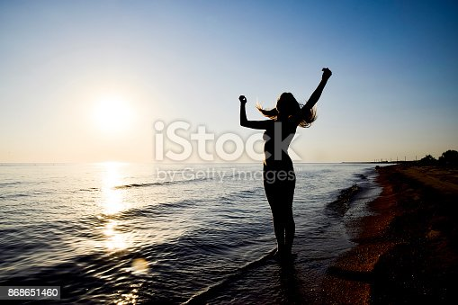 Silhouette of a girl against the sunset by the sea. The dark silhouette against the sea sunset. Girl on the beach in the evening.