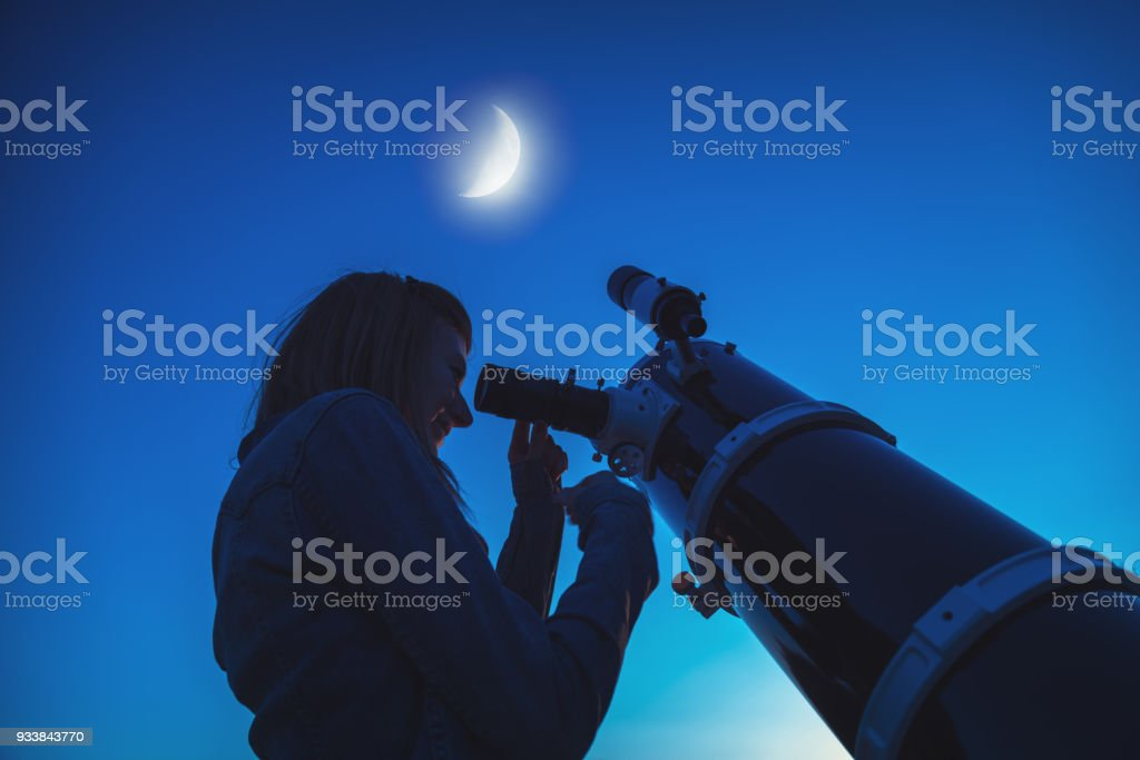 Silhouette of a girl and telescope with Moon on the sky. My astronomy work. stock photo