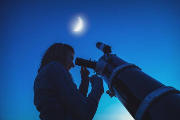 silhouette d'une jeune fille et le télescope avec la lune dans le ciel. mon travail d'astronomie. - astronomie photos et images de collection