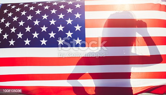 Young long haired girl stands behind the flag of United States.
