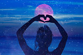 Silhouette of a girl holding heart-shape symbol for love on a starry night sky.