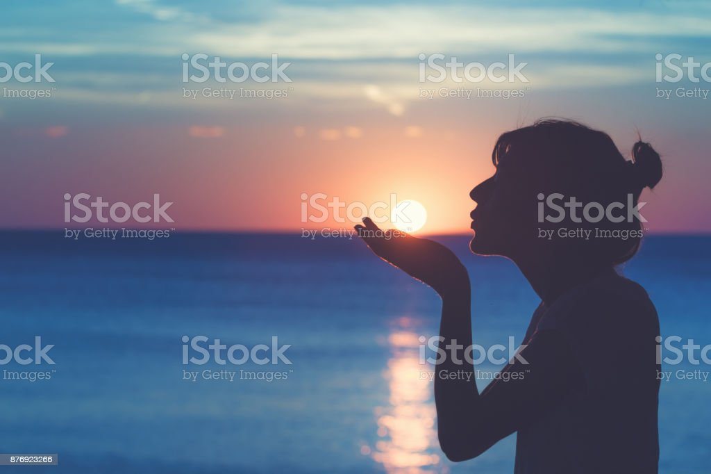 Silhouette of a girl kissing the sun with ocean / sea sunny background. stock photo