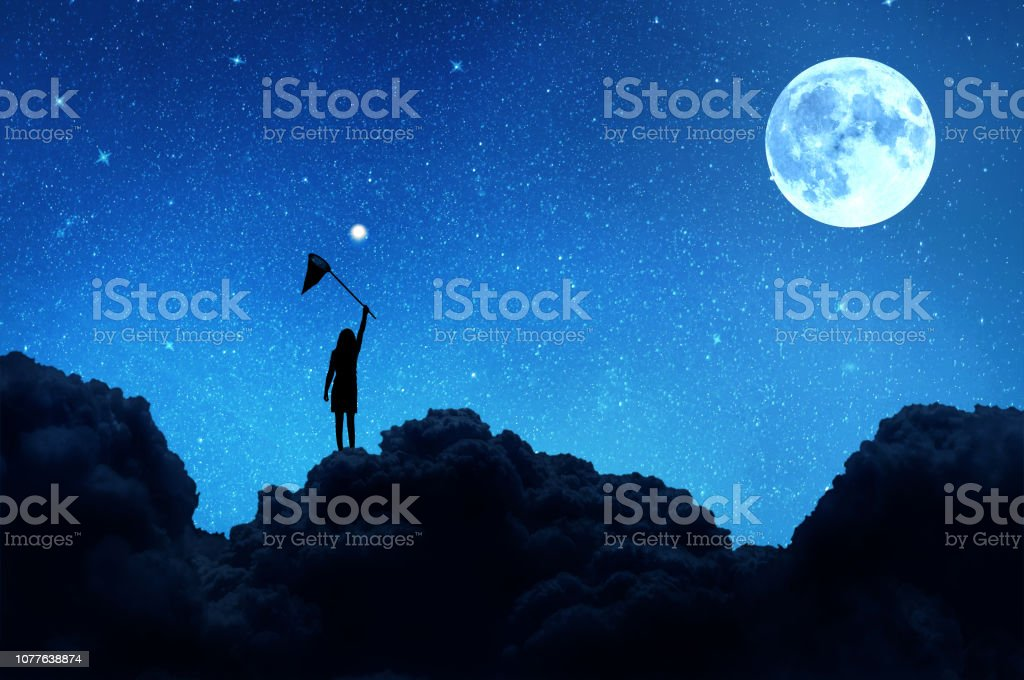 Silhouette of a girl standing on a cloud catches with a net a star...