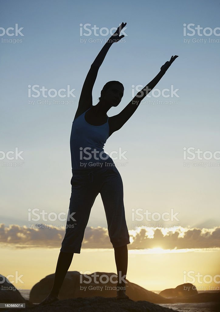Silhouette of a girl stretching hands at dawn royalty-free stock photo