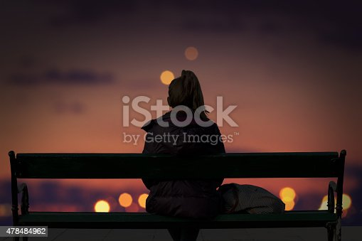 Silhouette of a girl watching defocused city lights.