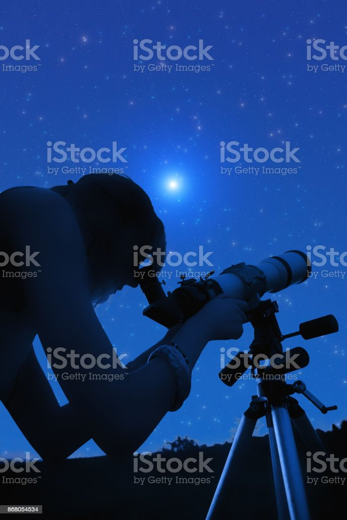 Silhouette of a girl while watching stars through the telescope in...