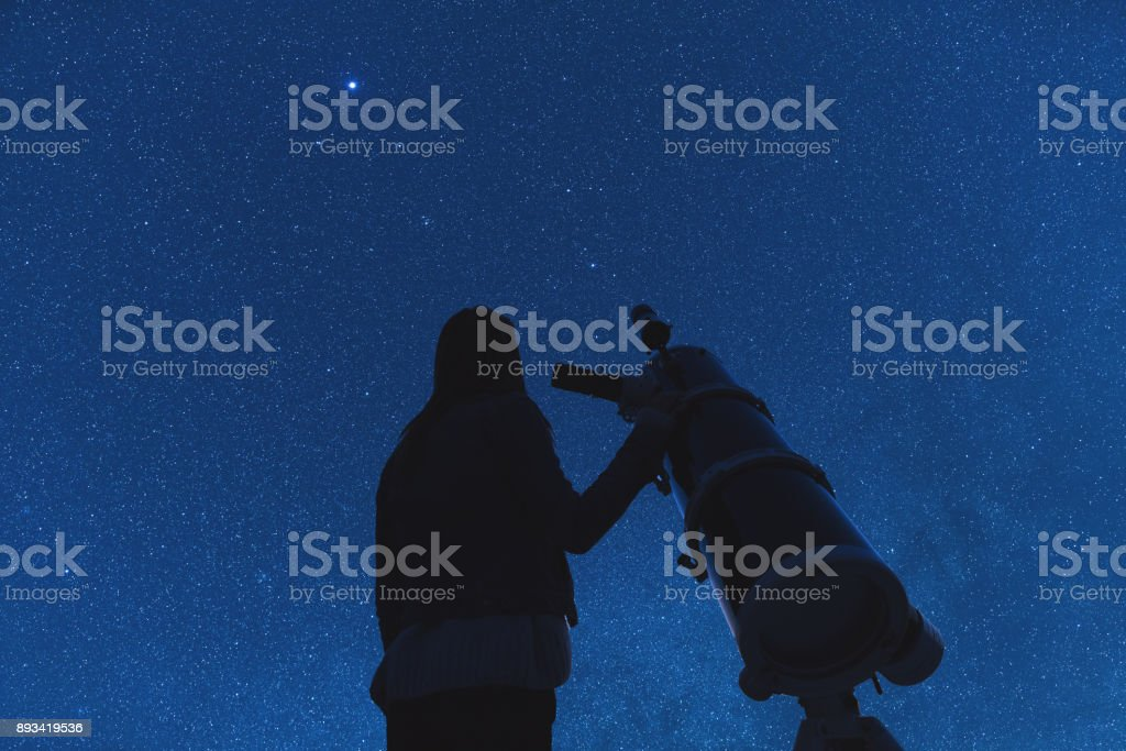Silhouette of a girl while watching stars through the telescope....