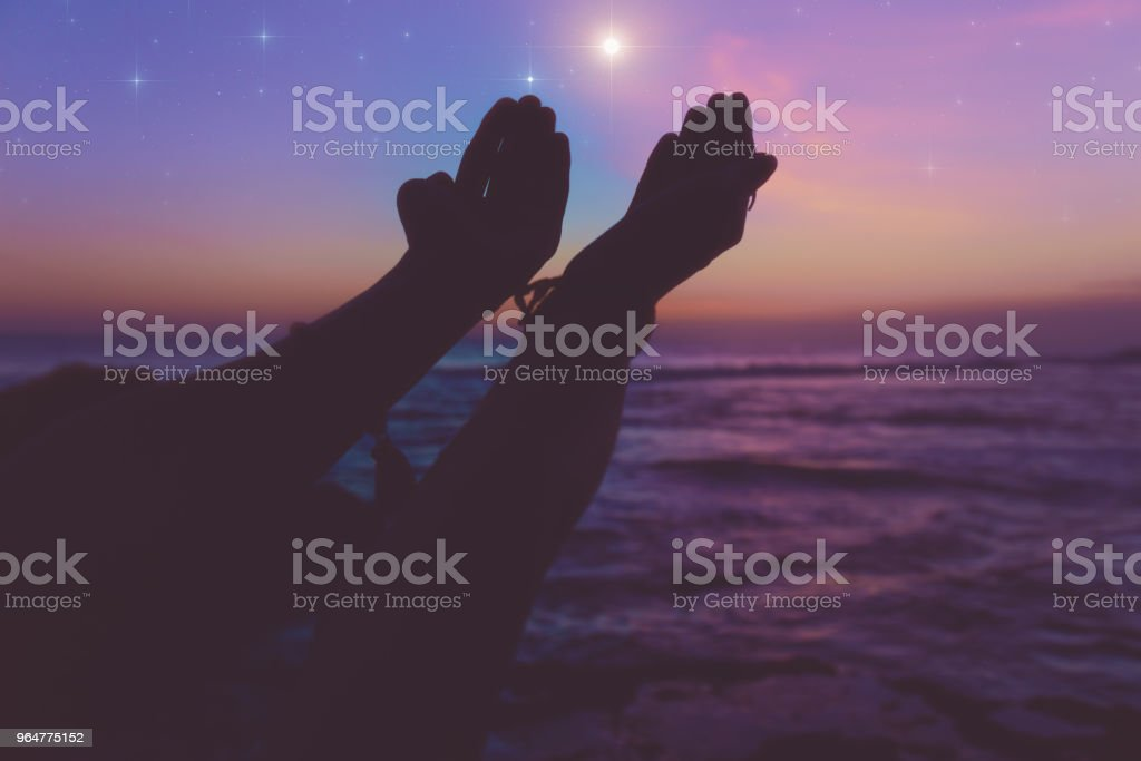 Silhouette of a girl with arms wide open in dusk / dawn and glittering stars above the ocean. My astronomy work. royalty-free stock photo