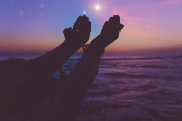 Silhouette of a girl with arms wide open in dusk / dawn and glittering stars above the ocean. My astronomy work. stock photo