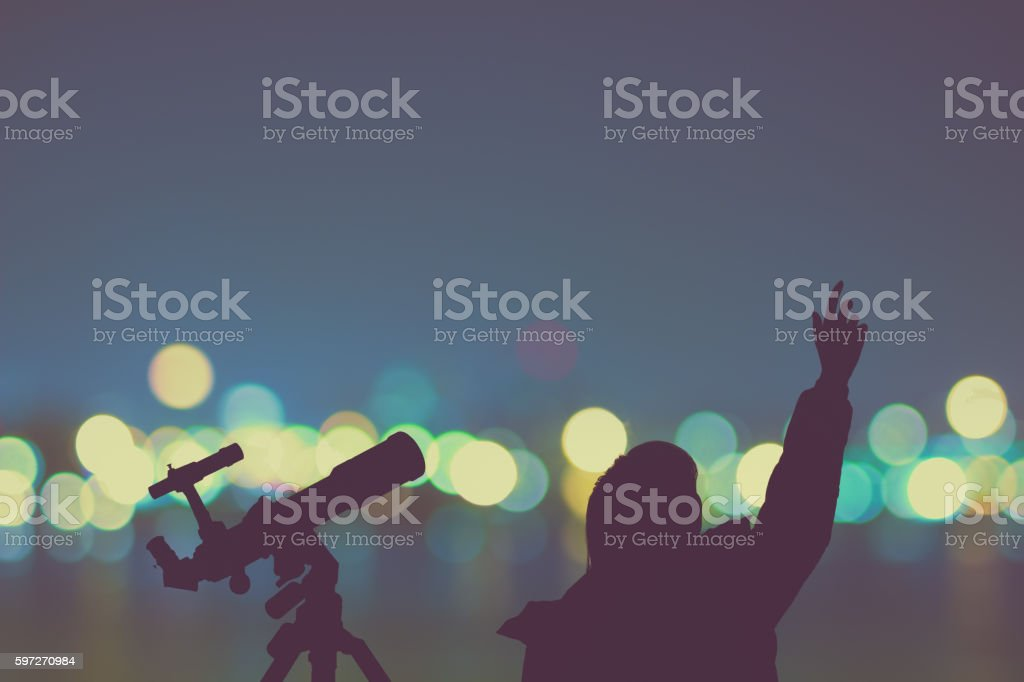 Silhouette of a girl with telescope and blurred city lights. Lizenzfreies stock-foto