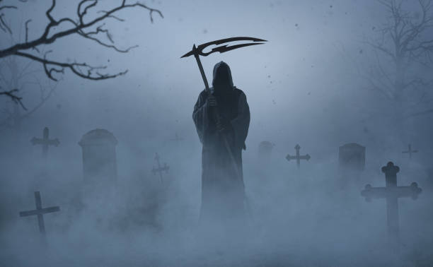 Silhouette of a grim reaper on a grave yard stock photo