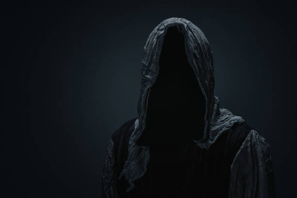 Silhouette of a grim reaper Silhouette of a Grim Reaper over dark gray background with copy space human skull stock pictures, royalty-free photos & images