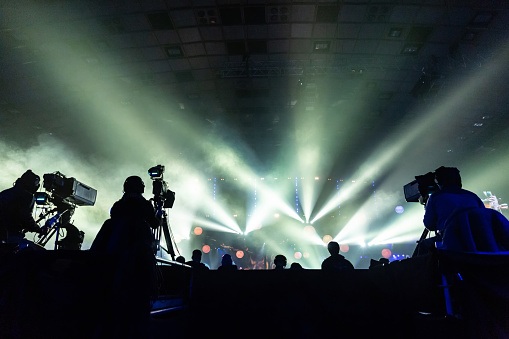 Silhouette of a group of cameramen broadcasting an event. Workers are on a high platform on the background of bright beams.