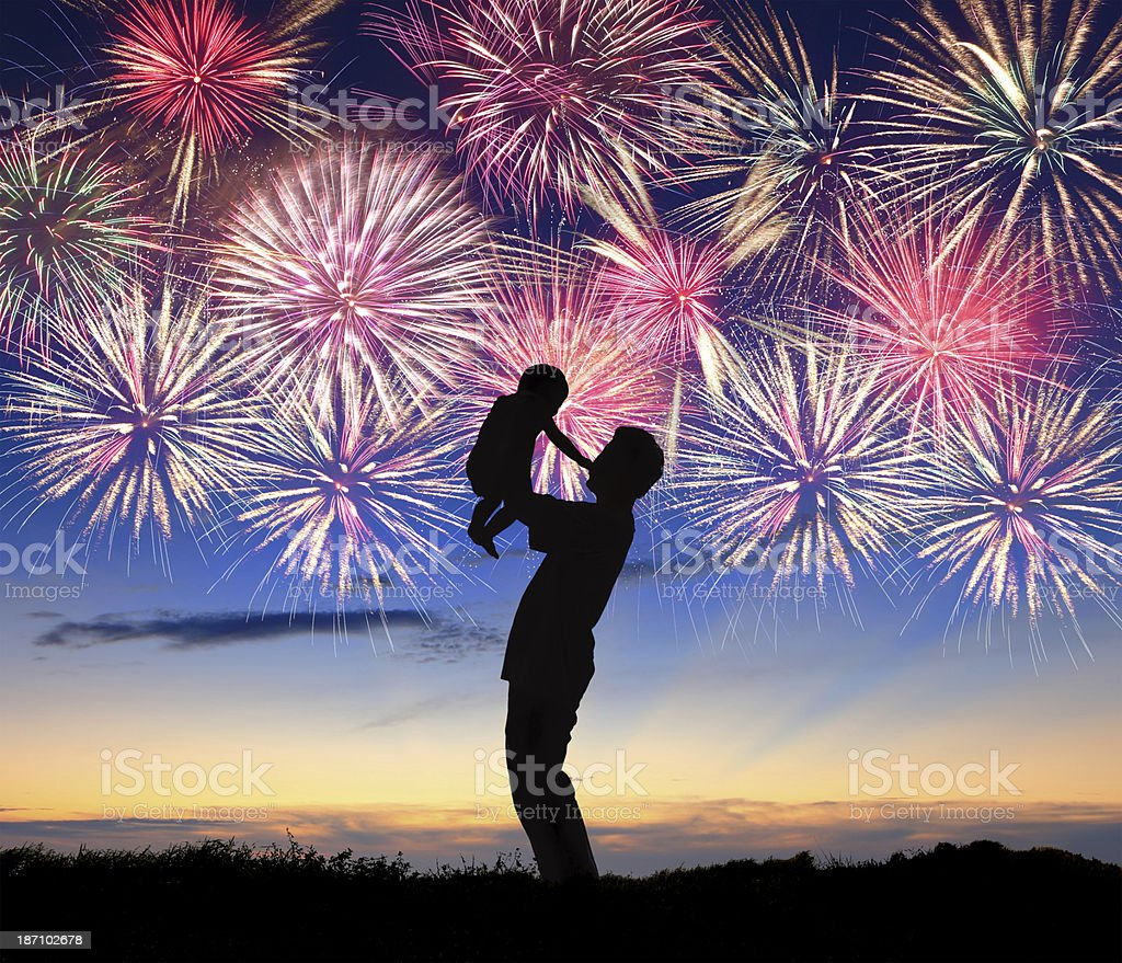 Silhouette of a happy family watching the fireworks stock photo