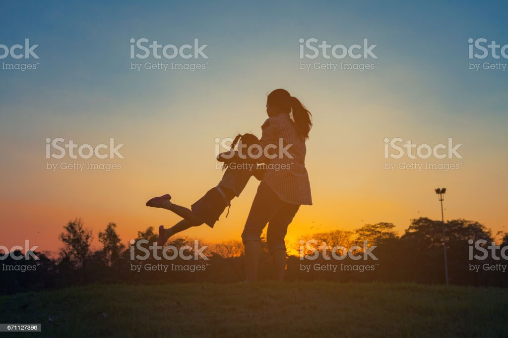 Silhouette of a happy little girl child running into the arms of his loving mother for a hug. stock photo