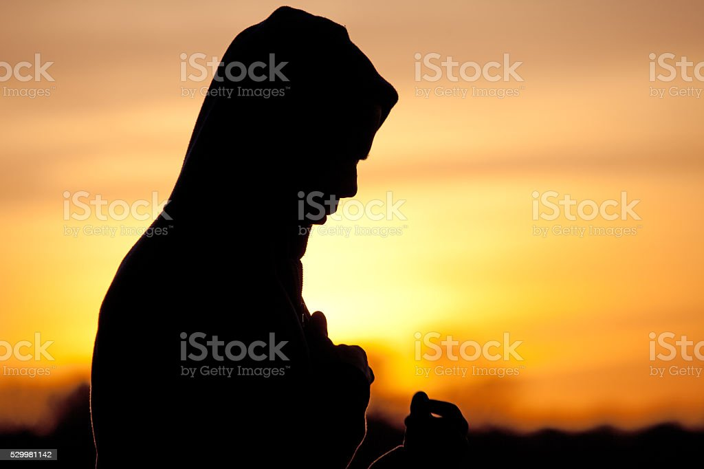 Silhouette of a hooded male at dawn stock photo