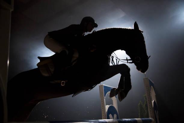 silhuetten av en häst och en ryttare som hoppar över hindret - hästhoppning bildbanksfoton och bilder