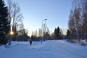 Winter time in Tampere forest with a walking human. Tampere is a city in Pirkanmaa, southern Finland. It is the most populous inland city in the Nordic countries.