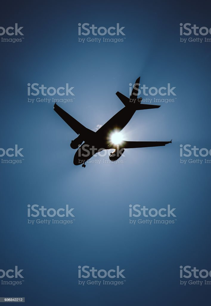 Silhouette of a jet plane in front of the bright sun stock photo