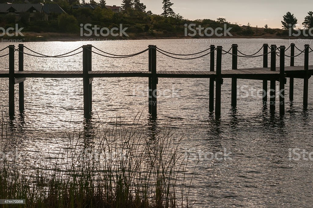 Silhouette of a jetty in a dam stock photo