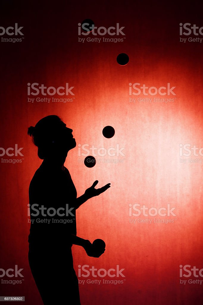 silhouette of a juggler with balls on a red background stock photo