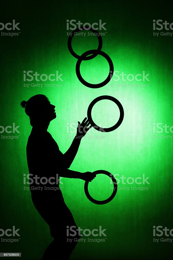 silhouette of a juggler with rings on a green background stock photo