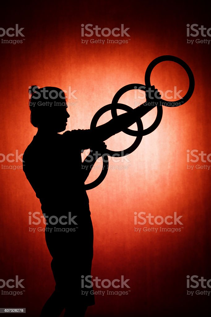 silhouette of a juggler with rings on a red background stock photo