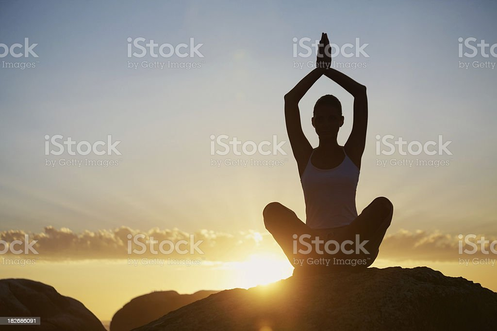 Silhouette of a lady practicing yoga at sunrise royalty-free stock photo