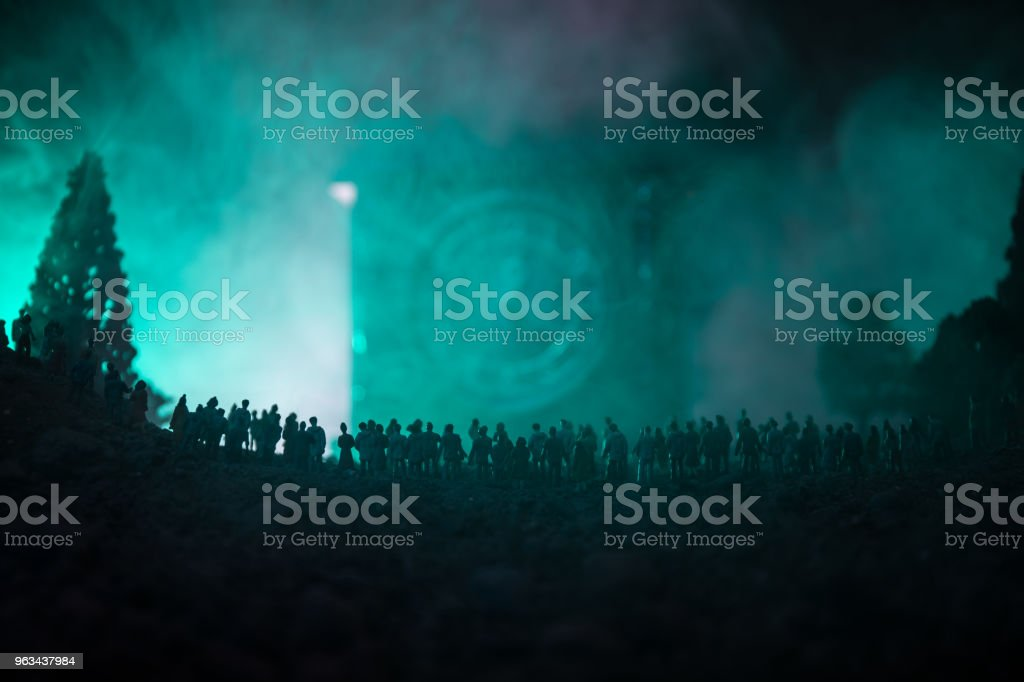 Silhouette of a large crowd of people in forest at night standing against a big arrow clock with toned light beams on foggy background. Time concept. - Zbiór zdjęć royalty-free (Biznes)