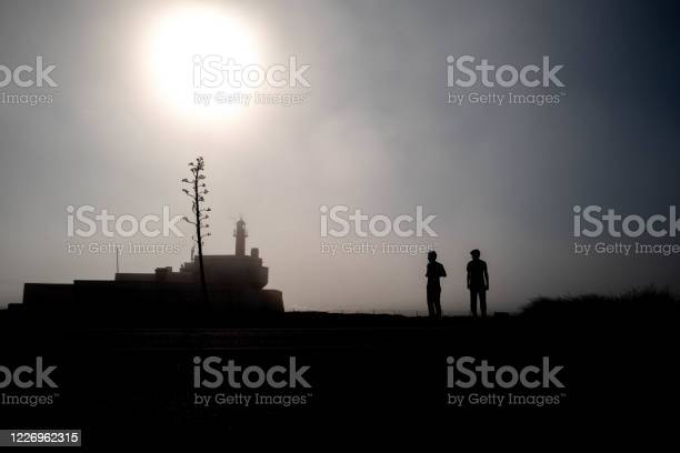 Photo of Silhouette of a lighthouse in the fog and two men on the Portuguese Atlantic coast.