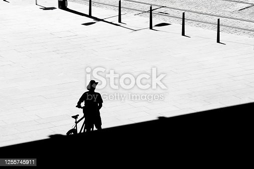812812808 istock photo Silhouette of a lonely cyclist walking from the shade  while crossing the town square on a hot summer day 1255745911