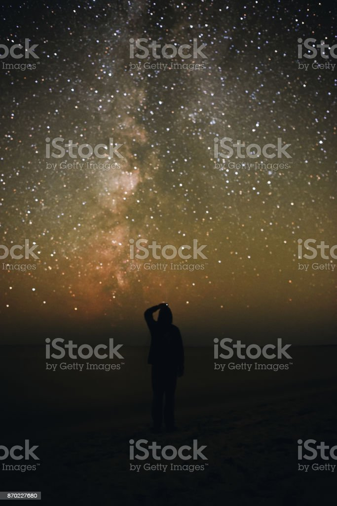 Silhouette of a lonely man standing on a sea beach and watching on the starry sky with Milky Way stock photo