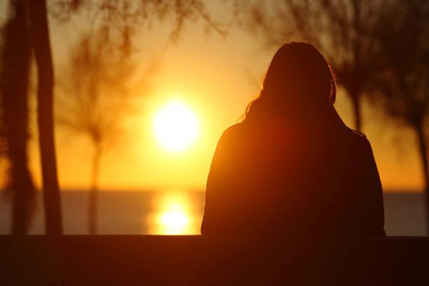 silhouette einer einsamen frau, sonnenuntergang im winter - totenfrau stock-fotos und bilder