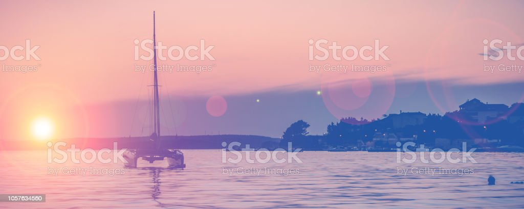 silhouette of a lonely yacht on sunset on Adriatic sea stock photo