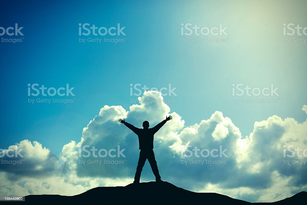 A silhouette of a male hiker standing on a mountain royalty-free stock photo
