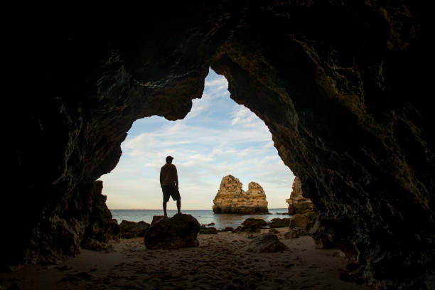 Silhouette of a male person at the cave entrance