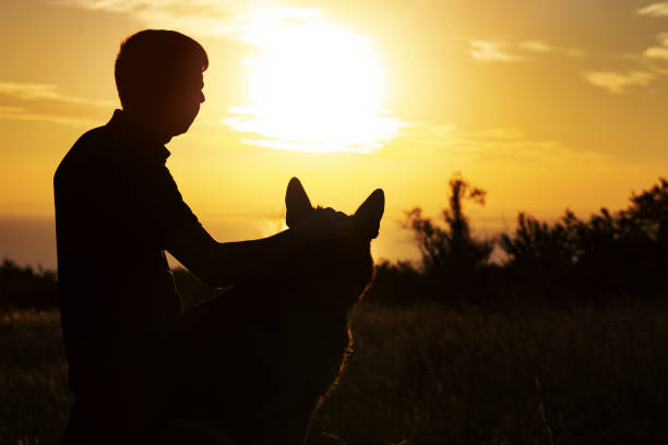 Silhouette of a man and a dog watching the sun set on the horizon in picture id1076763004?b=1&k=6&m=1076763004&s=612x612&w=0&h=u2n9qg8xhcq0 7 0vuywcdfmuev31upy9ug  spbze8=