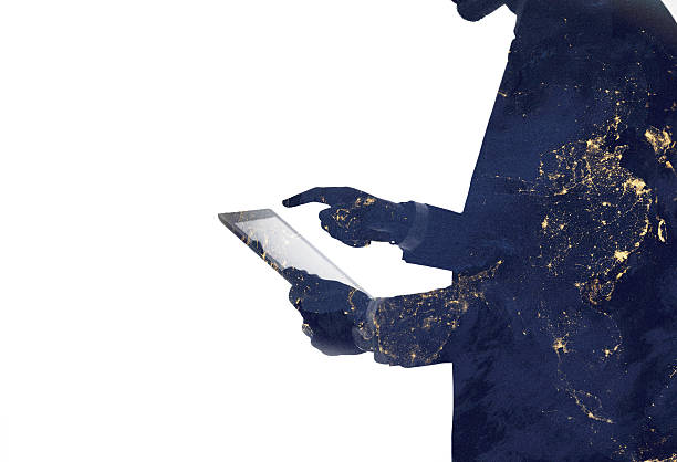 Silhouette of a man and digital tablet with galaxy overlaid stock photo