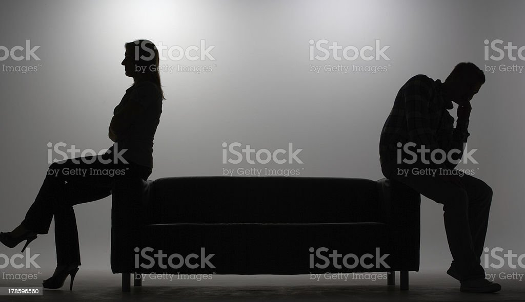 A silhouette of a man and woman sitting on a couch stock photo