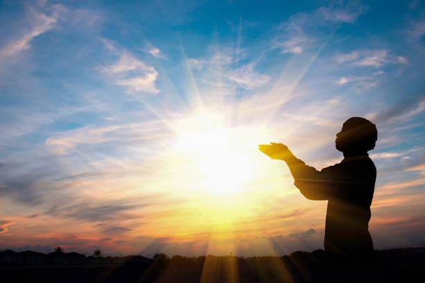 Silhouette eines Mannes beten über Sonnenuntergang Hintergrund – Foto