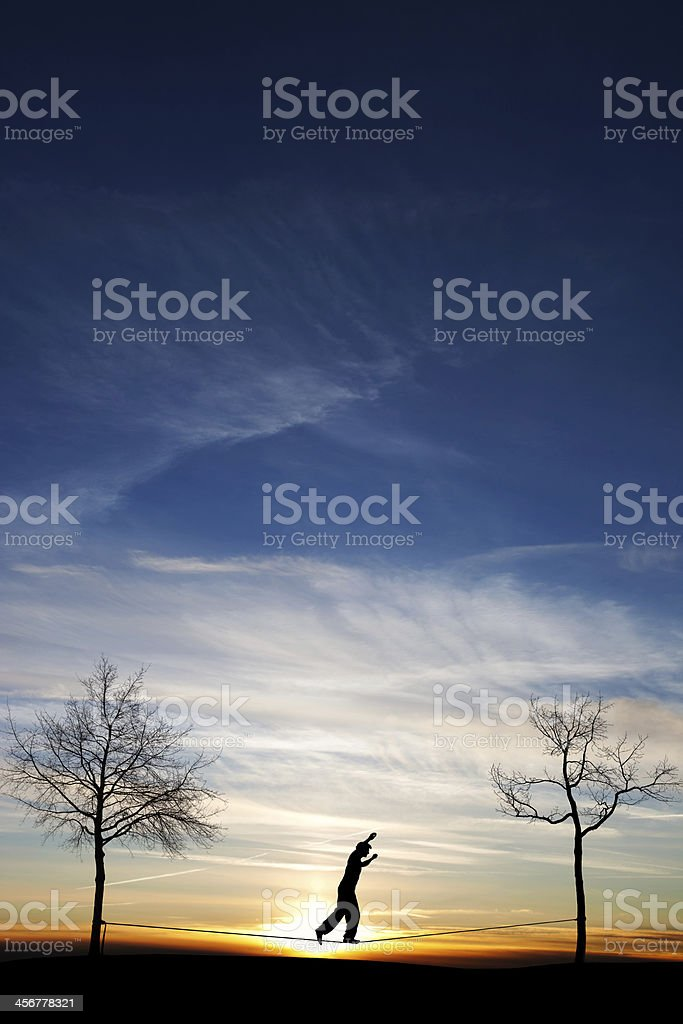 A silhouette of a man at sunset on a slack line stock photo