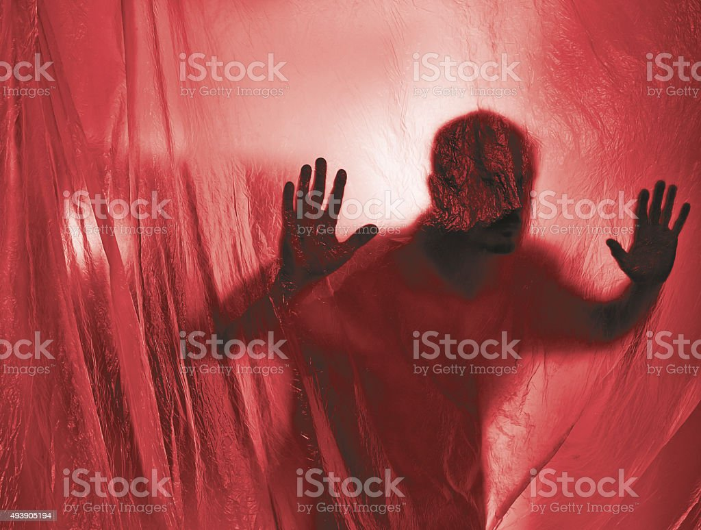Silhouette of a man behind a transparent plastic stock photo