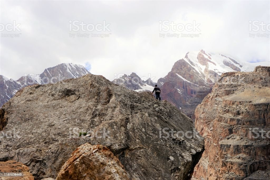 Man climbing on the steep rock, high altitude.
