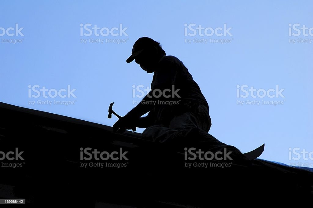 A silhouette of a man fixing the roof with a hammer stock photo