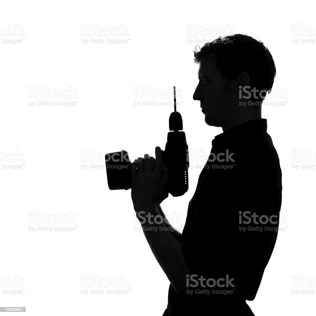 A silhouette of a man holding a drill royalty-free stock photo