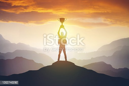 Silhouette of a man holding a trophy at sunset. Success concept