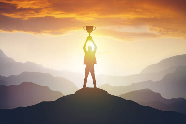 Silhouette of a man holding a trophy at sunset Silhouette of a man holding a trophy at sunset. Success concept win stock pictures, royalty-free photos & images