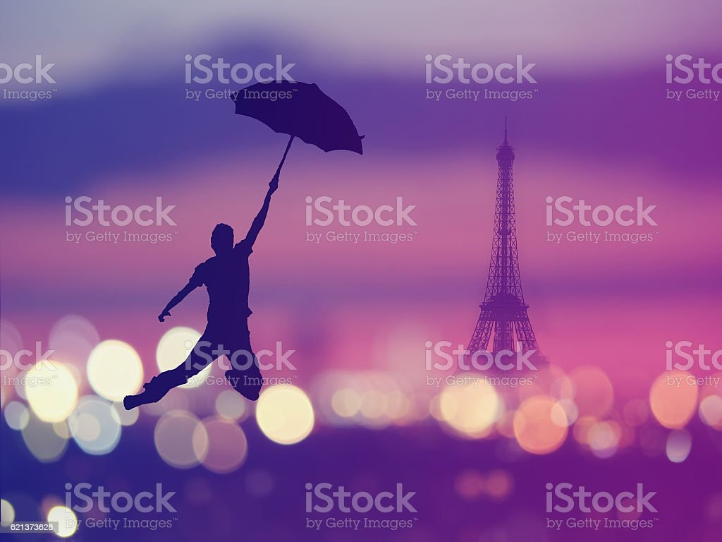 silhouette of a man holding umbrella flying over night Paris stock photo