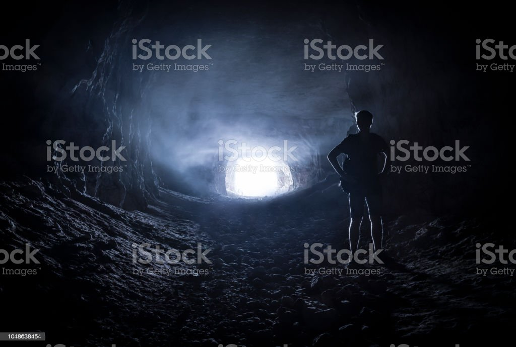 Silhouette of a man in a cave stock photo
