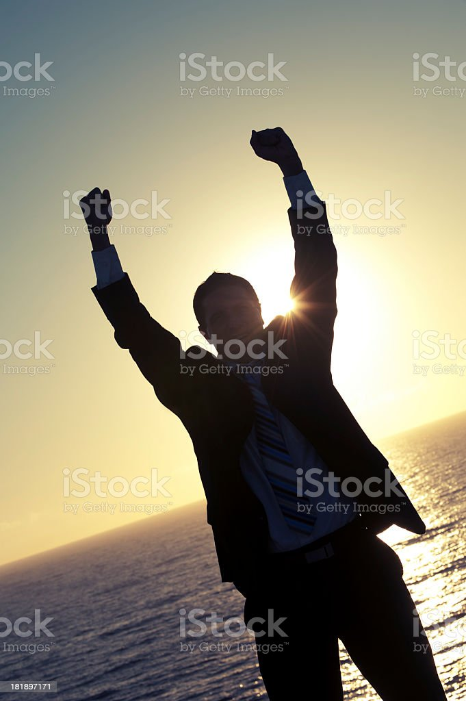 Silhouette of a man in a suit with raised arms royalty-free stock photo
